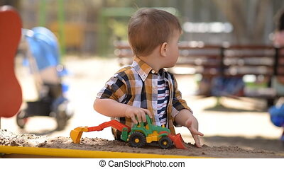 little child playing in the sandbox with a tractor - little...