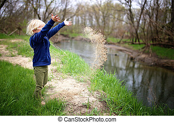 Little Child Playing Outside by the River, Throwing Sand in the Water