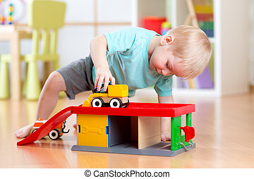 Little child toddler playing with a toy car in nursery