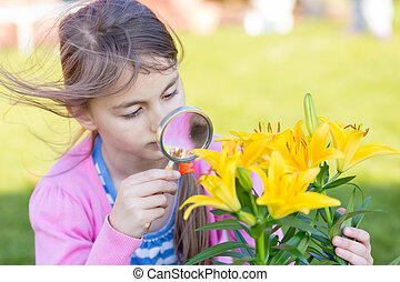 Little child playing with magnifying glass in a garden