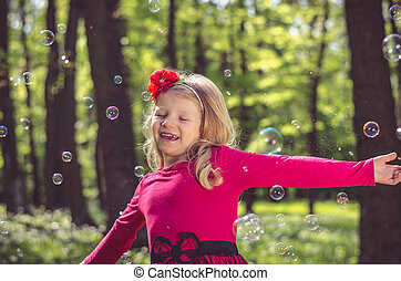 little child playing with soap bubbles