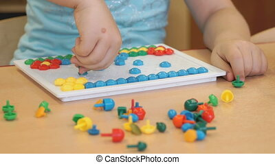 Little child plays a intellectual game at a table - Little...