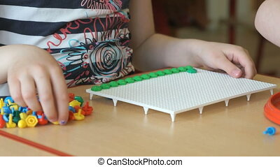 Little child plays a intellectual game at a table