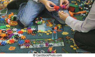 Little child plays in kindergarten indoors - Close-up of...