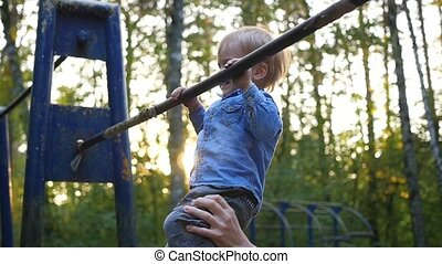 little child practicing on the horizontal bar