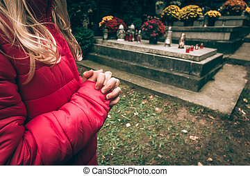 little child praying in the cemetery in autumn time