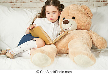 Little child reading to her plush friend