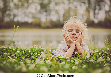 little child relaxing on the green grass in the river bank