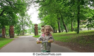 Little child ride scooter in park on summer day. Cute girl play outdoors