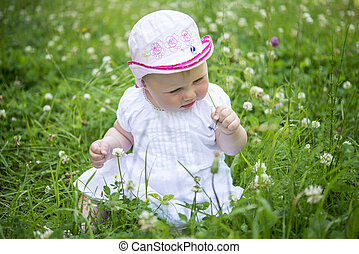 child sits in grass and looks at the flowers