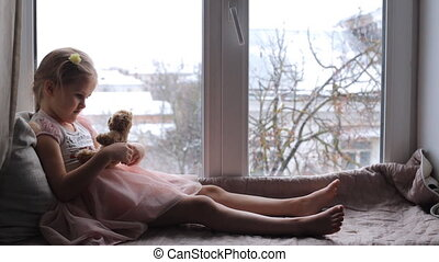 Little child sits on a windowsill with a teddy bear - Little...