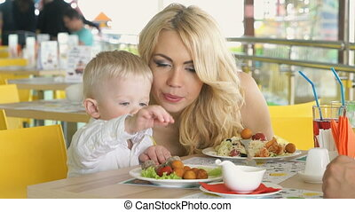 Little child sitting at table indulges with food