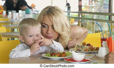 Little child sitting at table indulges with food - Two...