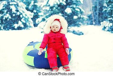 Little child sitting on sled in winter snowy day