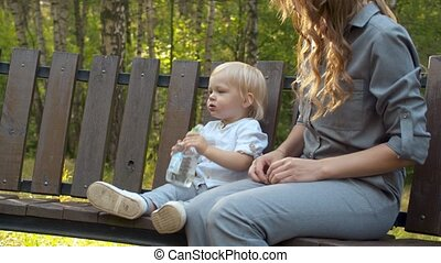 Little child sitting on the bench and drinking water