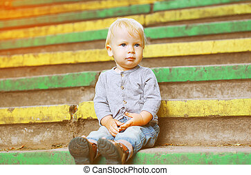 Little child sitting outdoors summer
