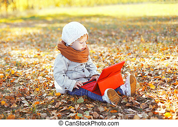 Little child sitting using tablet pc in autumn park