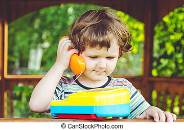 Little child talking on a toy phone.
