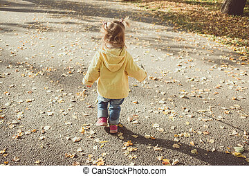 Little child walking on the road with autumn leaves