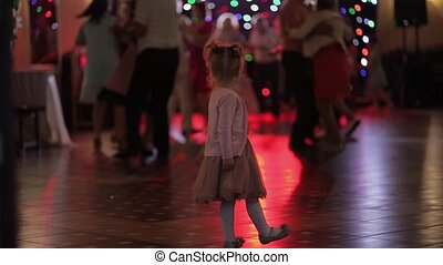 Little child watching adults dance in the patry. Feel...