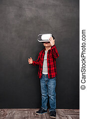 Little child wearing virtual reality device over blackboard