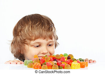 Little child with candies on white background