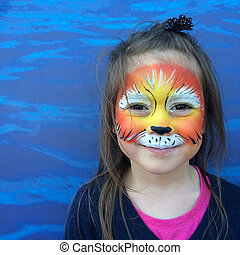 Little child (girl age 5-6) with lion face painting roaring like a lion.