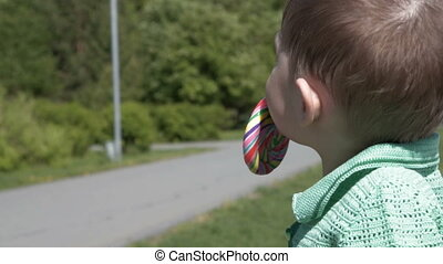 Little child with lollipop outdoor