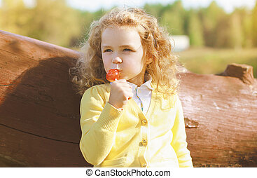 Little child with sweets having fun outdoors