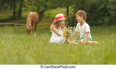 Little children are sitting on the lawn, the girl has a bouquet of flowers in her hands. Slow motion