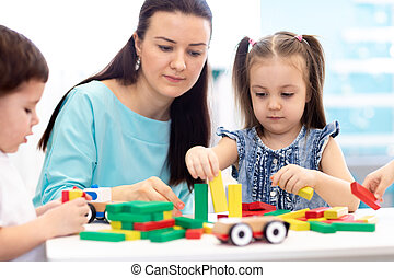 Little children building block toys at home or daycare. Kids playing with color blocks. Educational toys for preschool and kindergarten pupils.