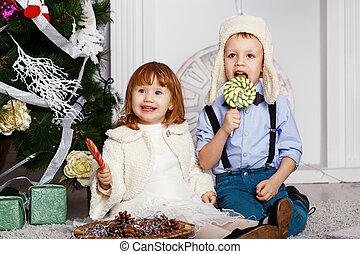 Little children eating a lollipops.