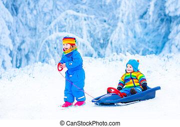 Little children enjoying a sleigh ride - Two little children...