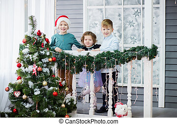 Little children In anticipation of new year and Christmas. Three little Kids are having fun and playing near Christmas tree