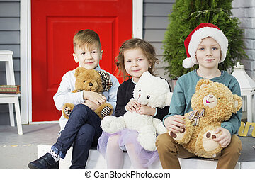 Little children In anticipation of new year and Christmas. Three little Kids are having fun and playing with teddy bears