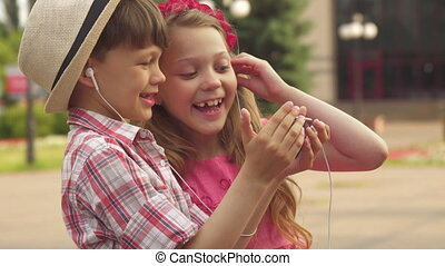 Little children play with smartphone outdoors