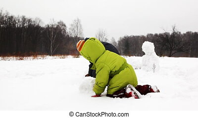 little children play with snow and make snowman