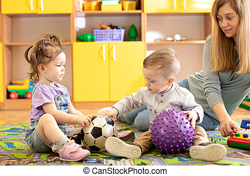 little children playing with balls in nursery