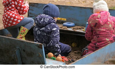 Little children playing with sand in sandbox outdoor in an...