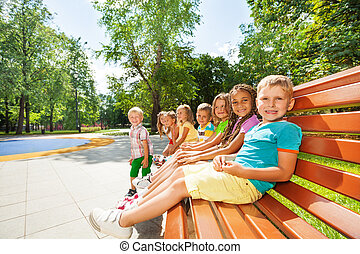 Little children rest on the bench in park