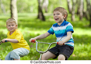 little children riding their bikes in park