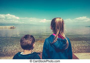 Little children standing on the lake shore