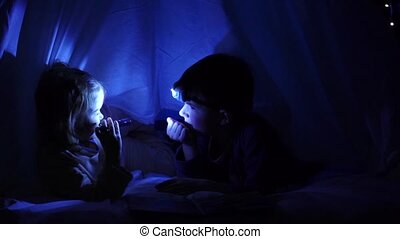 Little children lying on the bed playing under a blanket at night, shine on each other with a flashlight. Slow motion