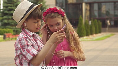 Little children watch something on smartphone outdoors