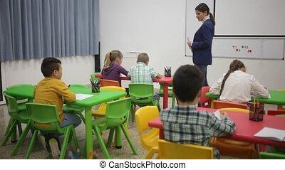 Little children working with teacher in classroom