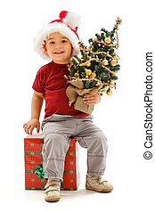 Little christmas boy sitting on present, holding Christmas tree