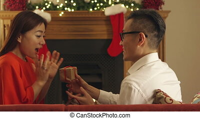 Little Christmas Surprise - Chinese couple sitting in their...