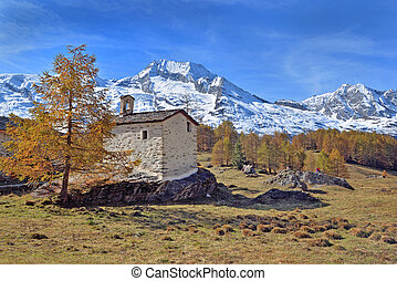 little church in french alpine national park in front of snowy mountain