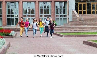 little classmates in casual clothes run along school yard - ...