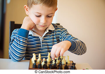 Little clever boy thinking with chess